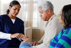 caregiver giving medicine to elderly patient
